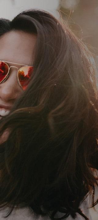 Mujer joven con anteojos de sol en