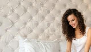 Cómo cuidar tu pelo en casa: una mujer sentada sobre una cama, sonriendo.