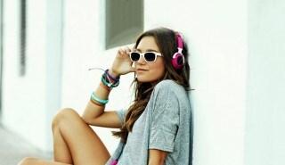 Mujer con pelo largo y lacio, sentada sobre un skate y escuchando música con auriculares para ilustrar la página de la línea Sedal Caspa Control.