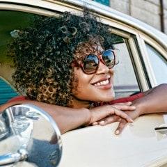 Mujer con cabello crespo sonriendo, con anteojos de sol, asomada por la ventanilla del auto.